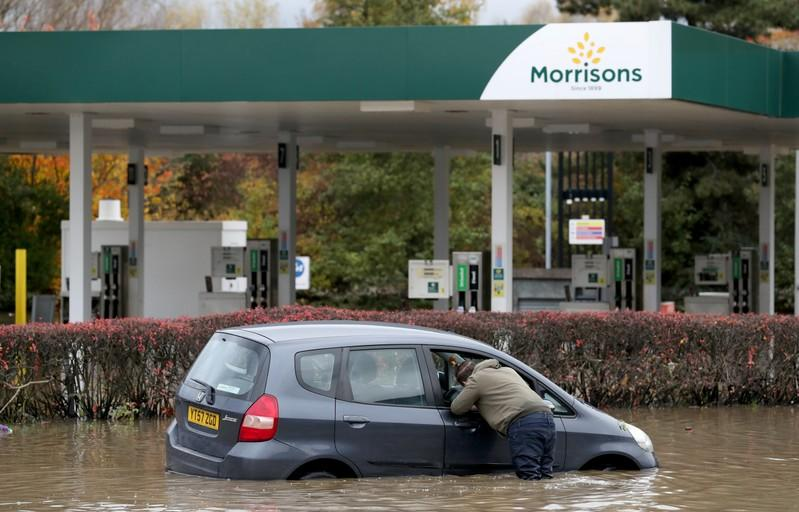 A man looks inside a car stranded in a flooded road in central Rotherham, near Sheffield