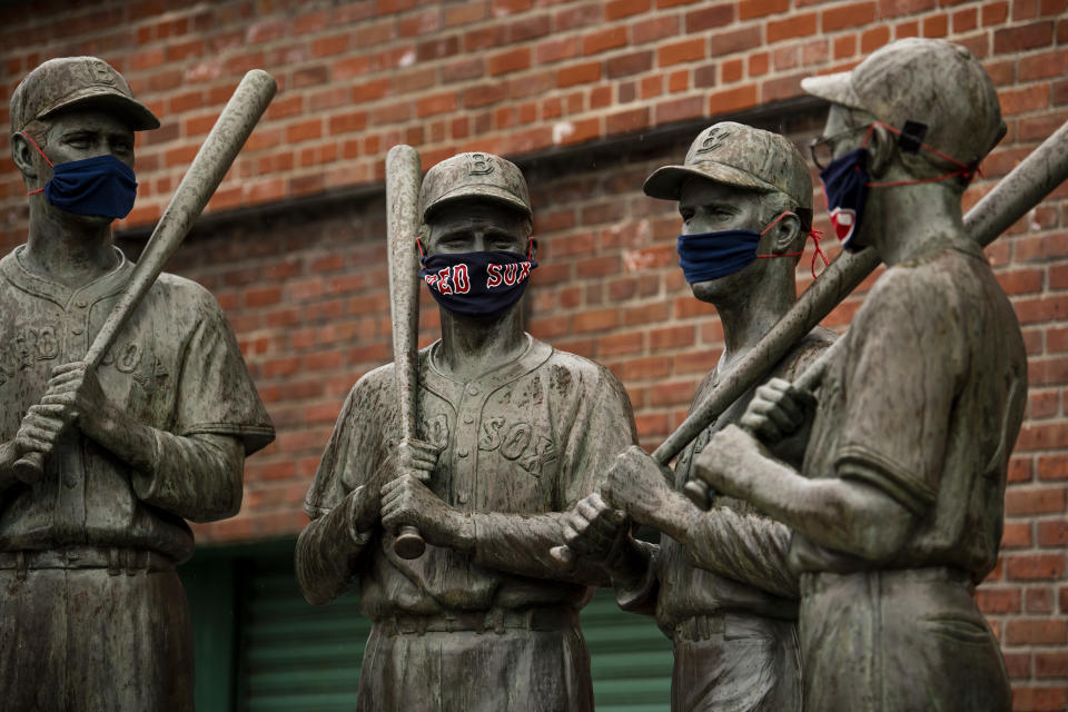 "BOSTON, MA - APRIL 9: The ""Teammates"" statues of former Boston Red Sox players Ted Williams, Bobby Doerr, Johnny Pesky and Dom DiMaggio wear makeshift masks made of Red Sox merchandise as the Major League Baseball season is postponed due the coronavirus pandemic on April 9, 2020 at Fenway Park in Boston, Massachusetts. (Photo by Billie Weiss/Boston Red Sox/Getty Images)"