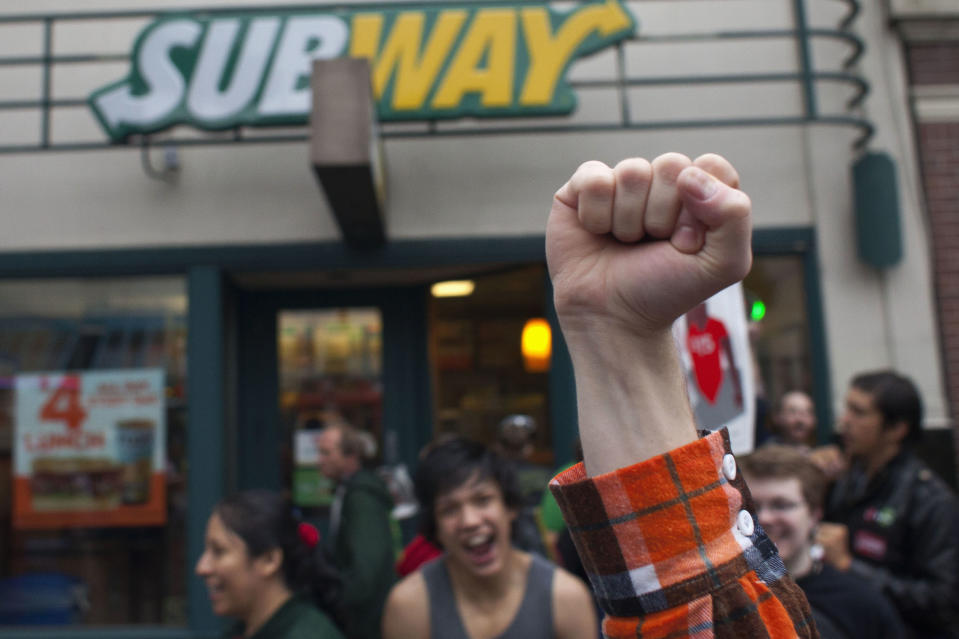 Stephen Baldwin holds his fist in the air outside a Subway restaurant during a strike aimed at the fast-food industry and the minimum wage in Seattle, Washington August 29, 2013. Fast-food workers went on strike and protested outside restaurants in 60 U.S. cities on Thursday, in the largest protest of an almost year-long campaign to raise service sector wages. REUTERS/David Ryder (UNITED STATES - Tags: CIVIL UNREST BUSINESS FOOD EMPLOYMENT)