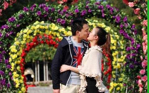 A couple kiss at Rose Garden of Yuntai Park, in Guangzhou, China. - Credit: ChinaFotoPress/Getty