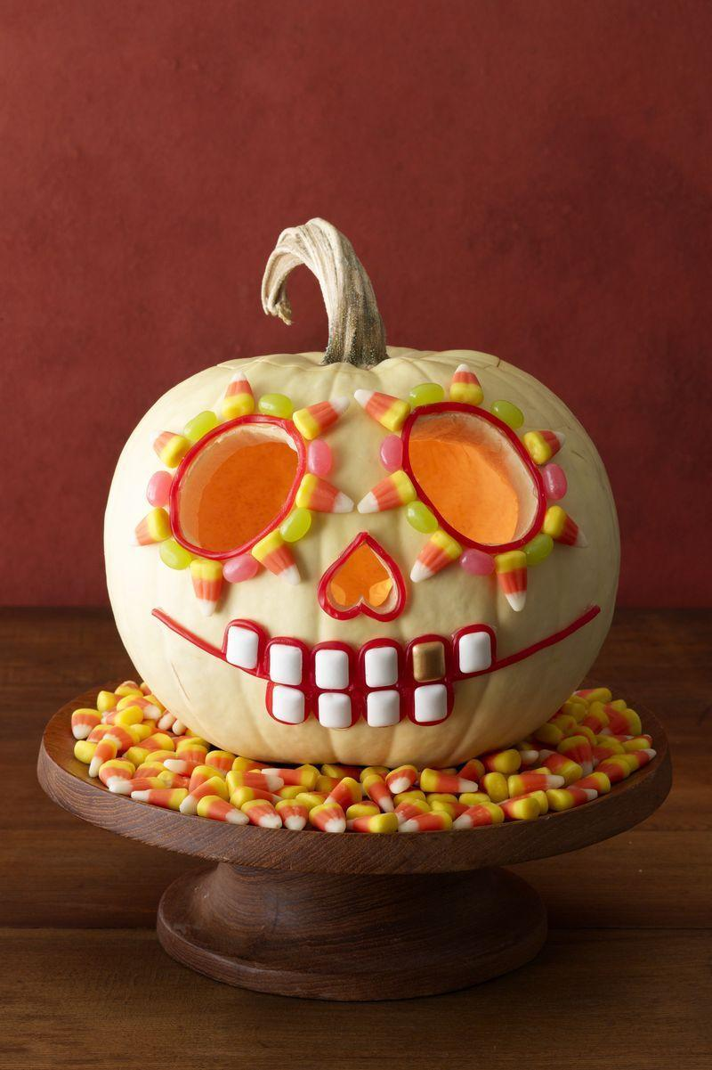 "<p>For this Day of the Dead skeleton, carve two ovals for eyes and an upside down heart for a nose in a hollowed-out white pumpkin. Decorate it by hot-gluing candy corn, jelly beans, licorice laces and <span class=""redactor-unlink"">square gum</span>, as shown. Paint one tooth gold.</p>"