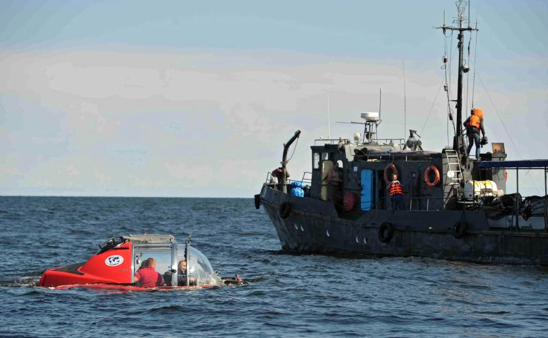 Russian President Vladimir Putin, left, submerges on board Sea Explorer 5 bathyscaphe off the island of Gogland 180 kilometers (110 miles) west of St. Petersburg, Russia, on Monday, July 15, 2013, Putin rode the small submersible craft 60 meters (200 feet) down to see the remains of the naval frigate Oleg, which sank in 1869, Russian news reports said. Putin's latest media event was modest by the stunt-happy Russian leader's standards, a half-hour trip to the bottom of the Gulf of Finland to see a shipwreck. (AP Photo/RIA-Novosti, Alexei Nikolsky, Presidential Press Service)