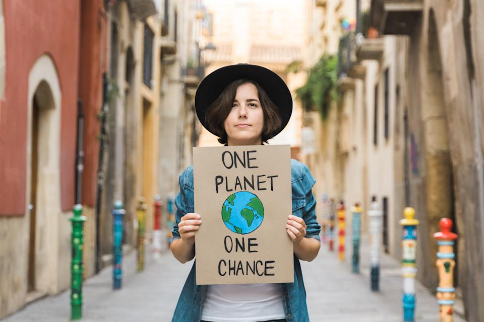 Millennial demonstrator protest for climate change outdoor in the city - Global warming, environment concept - Focus on girl holding banner