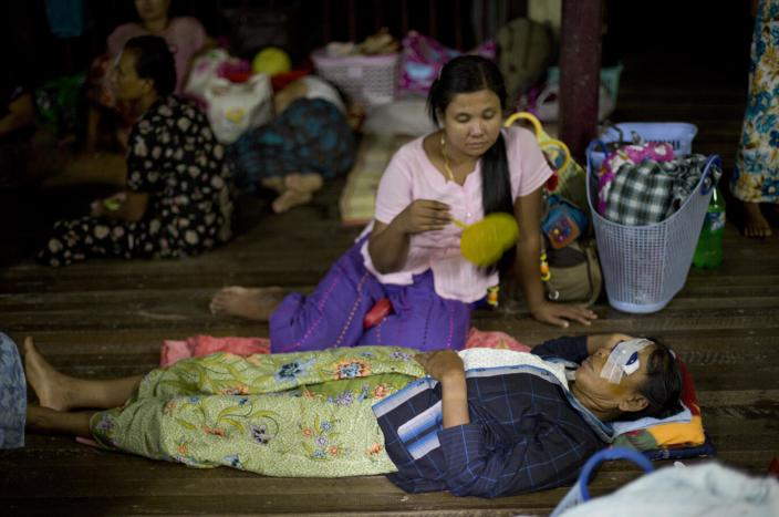"""In this Oct. 22, 2013 photo, a relative fans a patient with an eye patch who lies on the floor of a Buddhist monastery following a simple operation to remove a cataract in Bago, Myanmar. After decades of isolation and brutal military rule, the veil of darkness is starting to lift for Myanmar's blind, thanks to an """"assembly line"""" surgical procedure pioneered by Nepalese doctor Sandut Ruit that allows cataracts to be removed safely, without stitches, through two small incisions. New lenses are then carefully slipped in. (AP Photo/ Gemunu Amarasinghe)"""