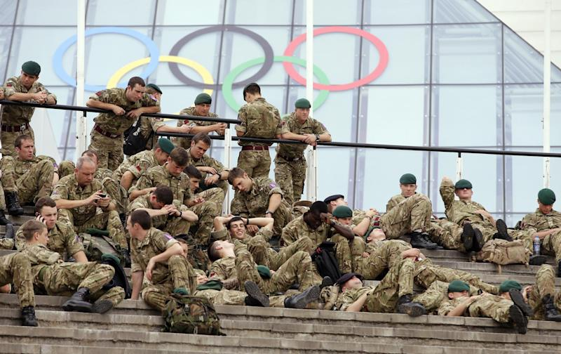 Members of the British military rest after working at the ExCel Centre at the 2012 Summer Olympics, Friday, July 27, 2012, in London. Competition begins at the venue on Saturday. (AP Photo/Andrew Medichini)