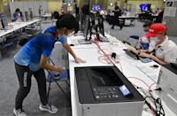 <p>A volunteer cleans a desk with alcohol tissue in the Main Press Centre in Tokyo on July 20, 2021, ahead of the Tokyo 2020 Olympic Games. (Photo by Jung Yeon-je / AFP)</p>
