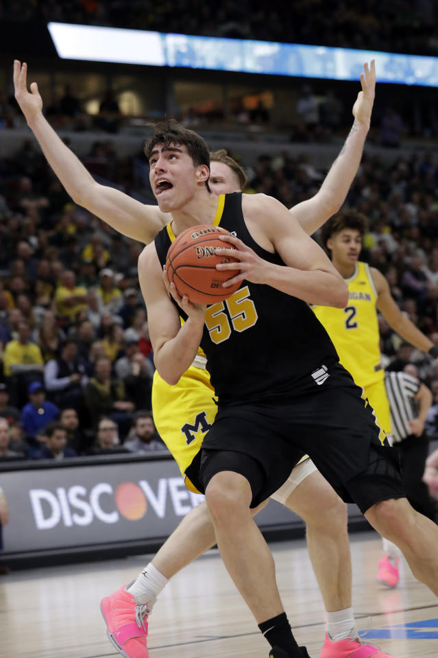 Iowa's Luka Garza (55) drives against Michigan's Ignas Brazdeikis during the first half of an NCAA college basketball game in the quarterfinals of the Big Ten Conference tournament, Friday, March 15, 2019, in Chicago. (AP Photo/Nam Y. Huh)