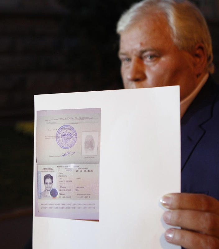 At a 2013 news conference in Moscow, lawyer Anatoly Kucherena shows a picture of Edward Snowden in the new refugee documents granted to him by Russia. (Photo: Maxim Shemetov/Reuters)