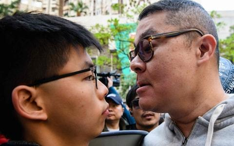 A man (R) faces off with pro-democracy campaigner Joshua Wong (L) as he and other campaigners gather to support by-election candidate Au Nok-hin (not seen) for the Legislative Council by-elections in Hong Kong on March 11, 2018 - Credit: AFP
