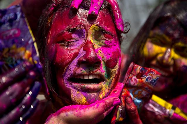 In this Thursday, March 21, 2019, file photo, an Indian girl grimaces as her face is smeared with colored powder during celebrations marking Holi, the Hindu festival of colors, in Gauhati, India. Holi also marks the advent of spring season. (AP Photo/Anupam Nath, File)