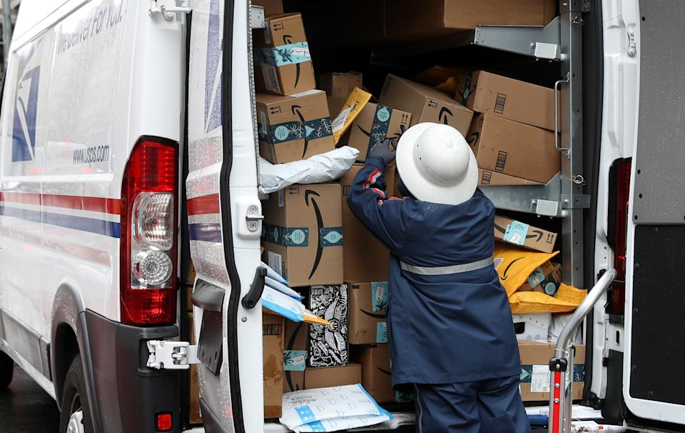 A U.S. Postal Service worker unpacks packages from a truck on December 02, 2019, in San Francisco, California. (Photo by Justin Sullivan/Getty Images)