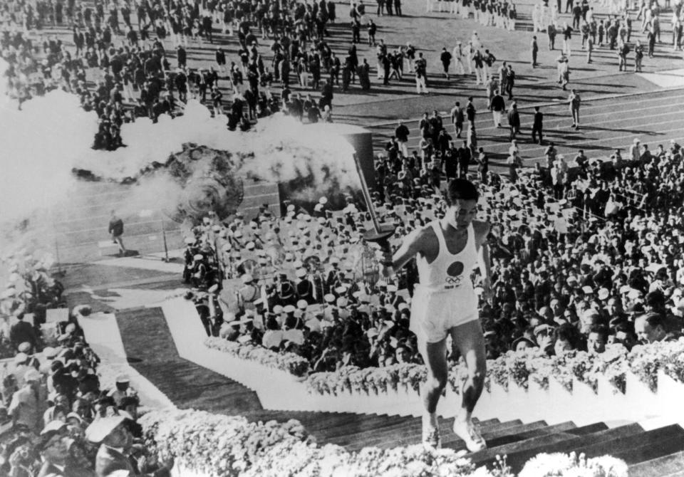 Japan's Yoshinori Sakai, who was born in Hironshima on the day the atomic bomb fell on the city in 1945, climbing up the stairs to light the Olympic cauldron at the 1964 Tokyo Summer Games.