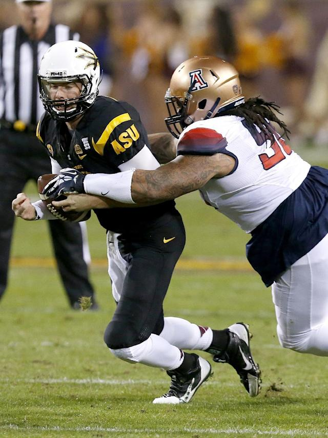 Arizona State's Taylor Kelly, left, gets sacked by Arizona's Tevin Hood during the first half of an NCAA college football game Saturday, Nov. 30, 2013, in Tempe, Ariz. (AP Photo/Ross D. Franklin)