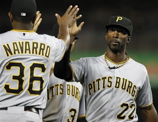 Pittsburgh Pirates center fielder Andrew McCutchen (22) high-fives Yamaico Navarro following their 5-3 victory over the Washington Nationals during a baseball game, Thursday, May 17, 2012, in Washington. McCutchen hit two home runs during the game. (AP Photo/Haraz N. Ghanbari)