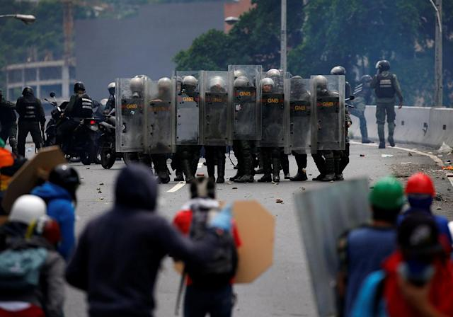<p>Riot police take position while clashing with opposition supporters rallying against President Nicolas Maduro in Caracas, Venezuela, May 3, 2017. (Carlos Garcia Rawlins/Reuters) </p>