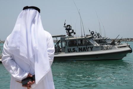 An Emirati official watches members of the U.S. Navy Fifth Fleet as they prepare to escort journalists to the Japanese-owned Kokuka Courageous tanker at a U.S. NAVCENT facility near the port of Fujairah