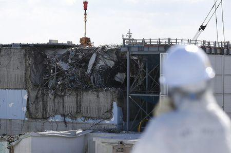 File photo of a member of the media looking at the No. 3 reactor building at Tokyo Electric Power Co's tsunami-crippled Fukushima Daiichi nuclear power plant in Okuma town