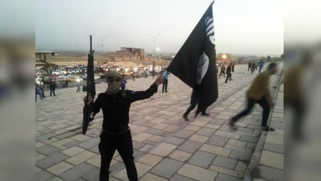 An Islamic State fighter holds an ISIL flag and a weapon in Mosul. Photo: Reuters
