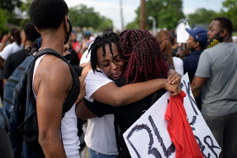 """George Floyd's niece Gabrielle Thompson, centre, cries as she hugs another woman during a """"Justice for George Floyd"""" event in Houston on May 30, 2020."""