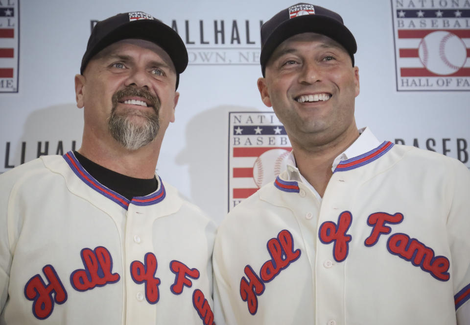 FILE - In this Jan. 22, 2020, file photo, New York Yankees shortstop Derek Jeter, right, and Colorado Rockies outfielder Larry Walker pose after receiving their Baseball Hall of Fame jerseys during a news conference in New York. (AP Photo/Bebeto Matthews, File)