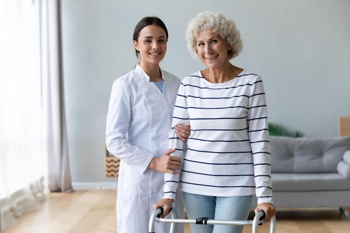 Female carer physiotherapist help happy old woman patient stand with walker.