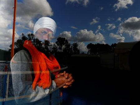 FILE PHOTO: A Sikh migrant worker looks through a window of the temple in Borgo Hermada, in the Pontine Marshes, south of Rome. Originally from India's Punjab state, the migrant workers pick fruit and vegetables for up to 13 hours a day for between 3-5 euros ($3.30-$5.50) an hour, in Bella Farnia, Italy May 19, 2019. REUTERS/Yara Nardi
