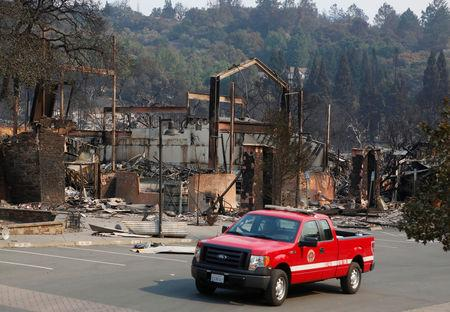 A firefighting crew drives pass a business destroyed in wildfire that tore through Santa Rosa, California