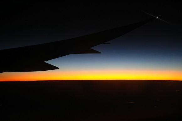 The wing of a Boeing Dreamliner in flight, silhouetted against the night sky.
