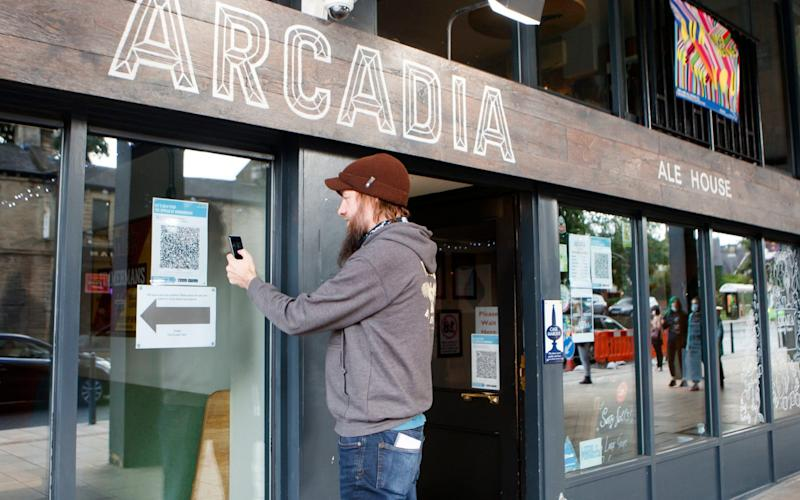 A man uses the Venue Check-in feature of the new NHS Covid-19 mobile phone application, to scan a QR code at the Arcadia Ale House in Leeds, after the app went live on Thursday morning - Danny Lawson/PA