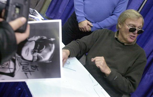 <p>A fan holds a Batman photograph signed by Adam West, right, at Cobo Hall during the 50th Autorama in Detroit, Saturday, Feb. 23, 2002. (Photo: Paul Warner/AP) </p>