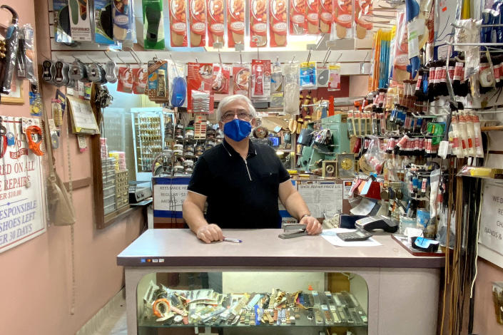 David Yushubayev, 67, stands at the counter of Markell's Shoe Repair in Midtown Manhattan, where business is