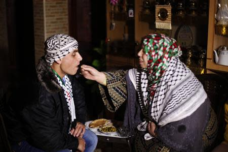 Freed Palestinian prisoner Rami Barbakh, who was held by Israel for 20 years, has his first breakfast with his mother after he was released, in Khan Younis in the southern Gaza Strip December 31, 2013. REUTERS/Ibraheem Abu Mustafa