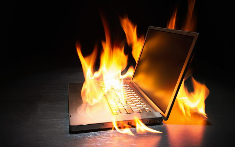 Laptop computer on fire - PM Images/Stone RF
