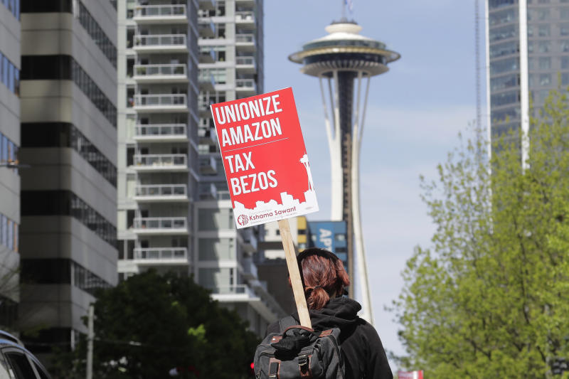 "FILE - In this May 1, 2020, file photo, a protester carries a sign that reads ""Unionize Amazon Tax Bezos,"" in reference to Amazon founder and CEO Jeff Bezos, while riding a bike during a car-based protest at the Amazon Spheres in downtown Seattle. Mary's Place, a family homeless shelter located nearby inside an Amazon corporate building on the tech giant's Seattle campus, marks a major civic contribution bestowed by Amazon to the hometown it has rapidly transformed. But the Mary's Place family homeless shelter also serves as a stark display of have-and-have-nots, given that some blame the tech giant's explosive growth over the past decade for making living in Seattle too costly for a growing number of people. (AP Photo/Ted S. Warren)"