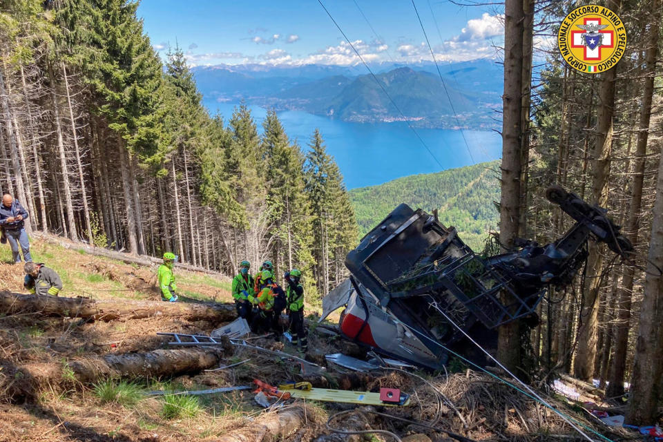Rescuers work by the wreckage of a cable car after it collapsed near the summit of the Stresa-Mottarone line in the Piedmont region, northern Italy, Sunday, May 23, 2021. A mountaintop cable car plunged to the ground in northern Italy on Sunday, killing at least five people and sending at least three more to the hospital, authorities said. (Soccorso Alpino e Speleologico Piemontese via AP)
