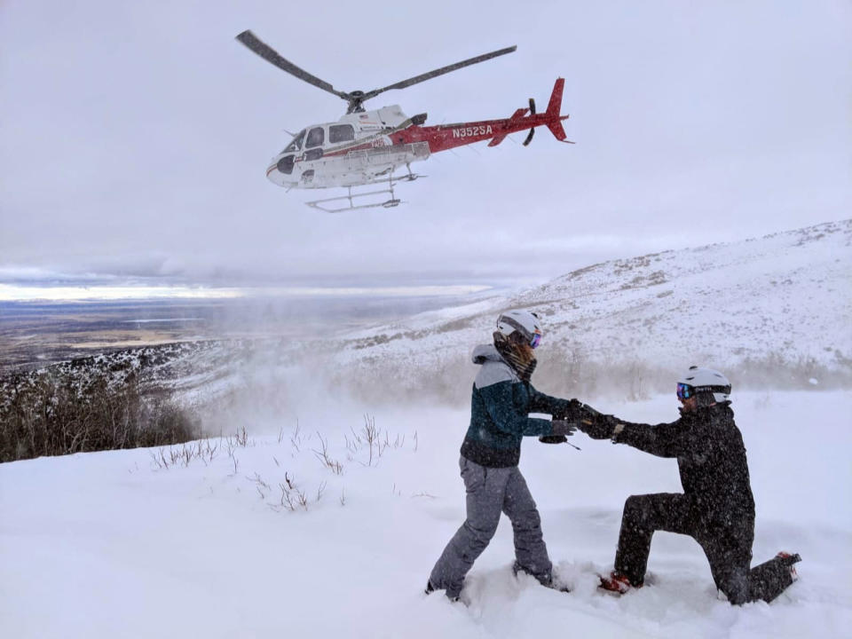 This Feb. 6, 2020 photo shows Jake Avery proposing to Kate Whiting while helicopter skiing in Nevada's Ruby Mountains. The two had been planning a 300-person wedding but decided to marry June 6 in their Northern California backyard, with a big party after the coronavirus pandemic settles. They're feeding a trend toward micro weddings that has grown stronger since the health crisis sent millions into isolation. (Mike Royer/Ruby Mountains Helicopter Experience via AP)