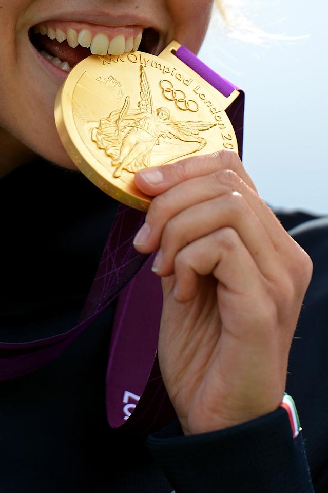Jessica Rossi of Italy bites the gold medal on the podium during the medal ceremony for the Women's Trap Shooting Finals on Day 8 of the London 2012 Olympic Game at the Royal Artillery Barracks on August 4, 2012 in London, England.  (Photo by Lars Baron/Getty Images)