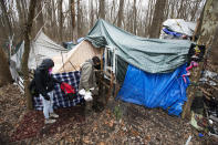 Jose Ortiz unlocks the gate to the residence he built in the homeless encampment known as the Jungle on Monday, Dec. 7, 2020, in Ithaca, N.Y.. His friend Tas'a Towsley is with him. (AP Photo/John Munson)