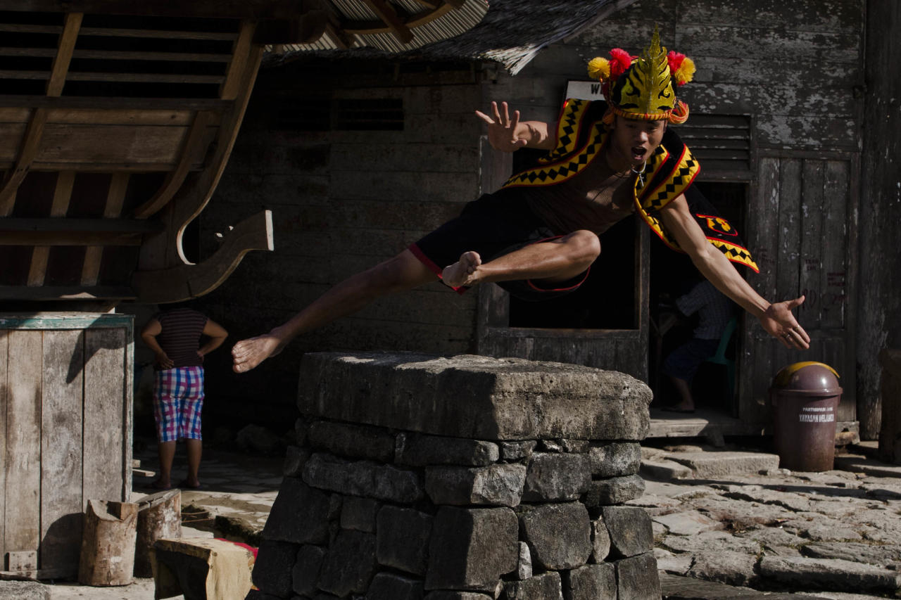 NIAS ISLAND, INDONESIA - FEBRUARY 22:  A villager wearing traditional costume jumps over a stone in front of their ancient houses in Bawomataluwo village on February 22, 2013 in Nias Island, Indonesia. Stone Jumping is a traditional ritual, with locals leaping over large stone towers, which in the past resulted in serious injury and death. Stone jumping in Nias Island was originally a tradition born of the habit of inter tribal fighting on the island of Nias.  (Photo by Ulet Ifansasti/Getty Images)