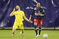 Nashville SC defender Walker Zimmerman (25) falls after colliding with New England Revolution forward Teal Bunbury (10) during the first half of an MLS soccer match Friday, Oct. 23, 2020, in Nashville, Tenn. (AP Photo/Mark Humphrey)