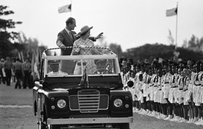 FILE - In this Wednesday, Oct. 15, 1977 file photo, Britain's Queen Elizabeth II and Prince Philip wave to young people at Nassau's Clifford Park after their arrival in Nassau, Bahamas. Buckingham Palace says Prince Philip, husband of Queen Elizabeth II, has died aged 99. (AP Photo/File)