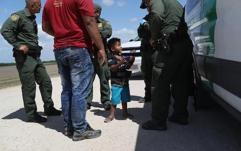 A boy and father from Honduras are taken into custody - Credit: Getty