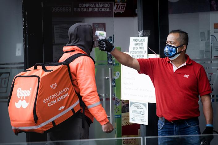 """A guard at a store checks the temperature of a delivery driver in Quito, Ecuador, during the government lockdown to prevent the spread of COVID-19.<span class=""""copyright"""">Isadora Romero—Magnum Foundation</span>"""