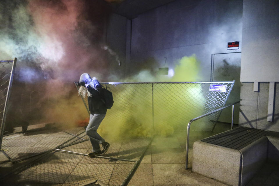 A protesters runs as police respond during a demonstration, Friday, July 17, 2020 in Portland, Ore. Militarized federal agents deployed by the president to Portland, Oregon, fired tear gas against protesters again overnight as the city's mayor demanded that the agents be removed and as the state's attorney general vowed to seek a restraining order against them. (Dave Killen/The Oregonian via AP)