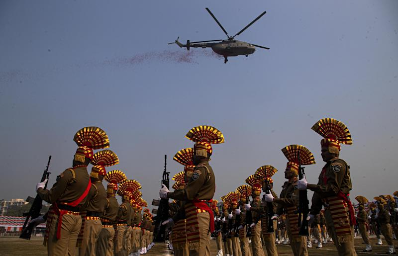 Helicopter flies over marching soldiers