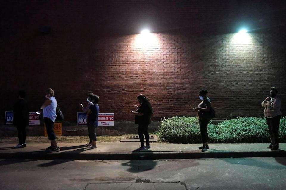 People wait in line to cast their ballots in early voting in Houston, Texas, on 13 October.