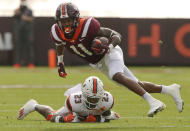 Virginia Tech's Tré Turner 11 turns upfield after catching a pass from quarterback Hendon Hooker past Miami defender Te'Cory Couch during the first half of an NCAA college football game Saturday, Nov. 14, 2020, in Blacksburg, Va. (Matt Gentry/The Roanoke Times via AP, Pool)