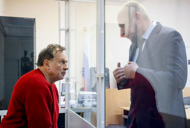Oleg Sokolov, a history professor at St Petersburg State University listens to his lawyer sitting in a cage waiting for a court session in St Petersburg, Russia.