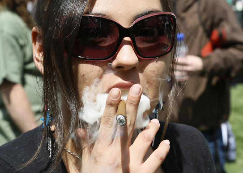 A woman smokes a blunt at the 4/20 marijuana holiday in Civic Center Park in downtown Denver April 20, 2013. REUTERS/Rick Wilking (UNITED STATES - Tags: HEALTH SOCIETY POLITICS)