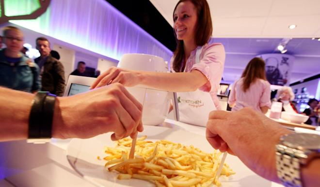A woman serves up french fries prepared in a Philips AirFryer. Photo: Getty Images
